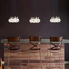 Three Clusters of TECH Lighting Mina Pendant Lights over a bar